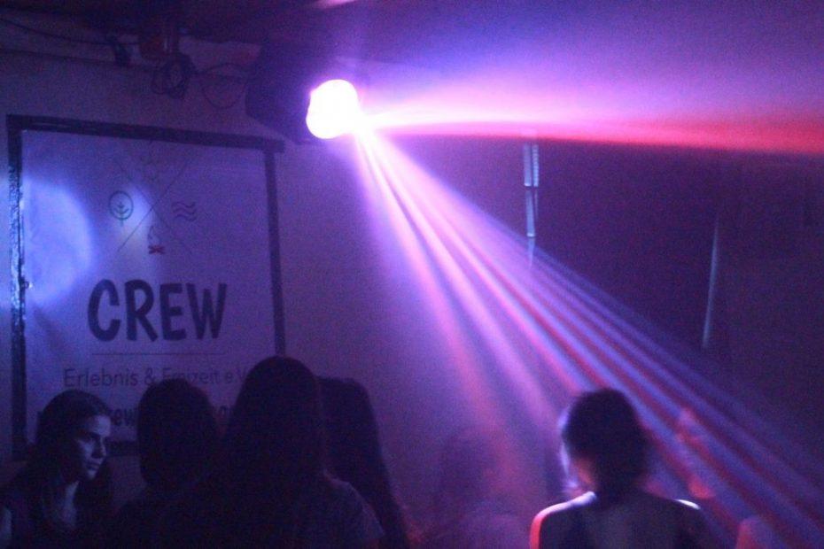 Eine Lampe strahlt Licht auf auf eine Gruppe Jugendlicher die auf einer Party feiern