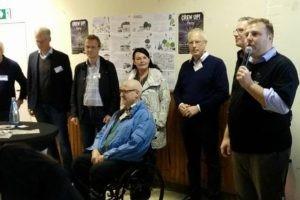 Eine Gruppe Politiker steht vor einer Wand zusammen mit einem Moderator