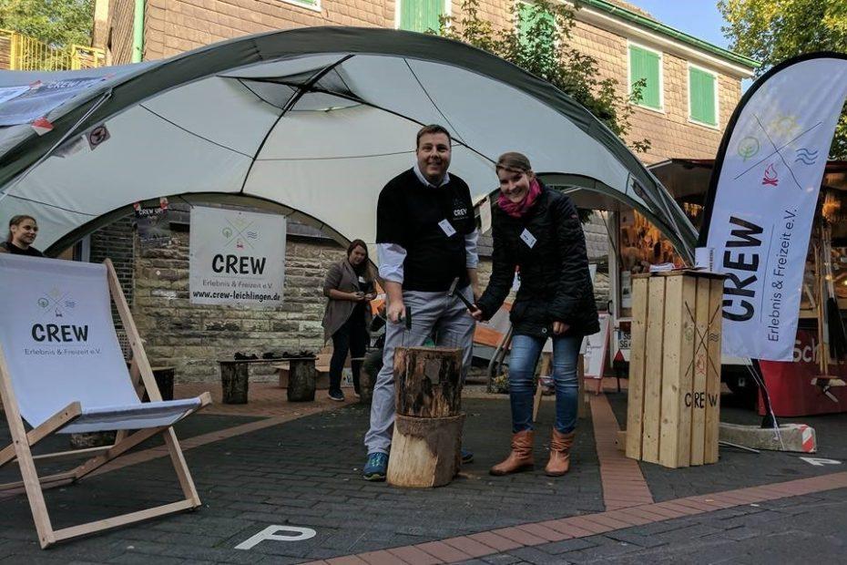 Zwei Menschen stehen unter einem Pavillon hinter einem Holzstumpf und halten Hämmer in den Händen
