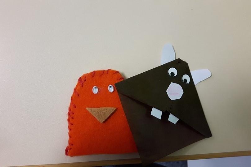 Gebastlelte Figuren aus Stoff und Pappe liegen auf einem Tisch