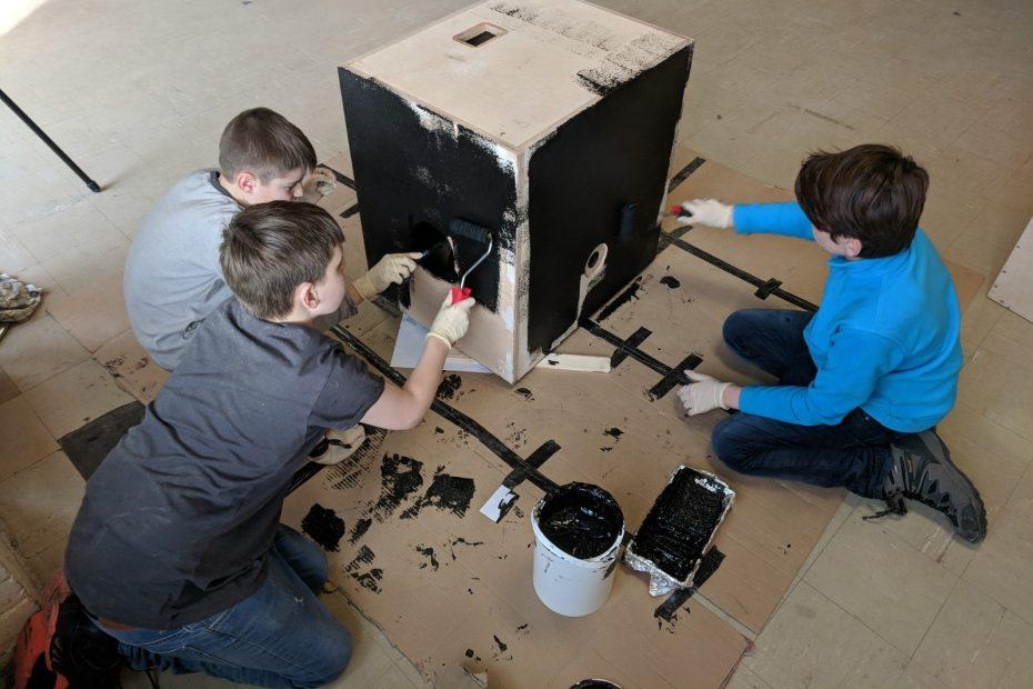 Drei Jugendliche bemalen eine Holzbox mit schwarzer Farbe