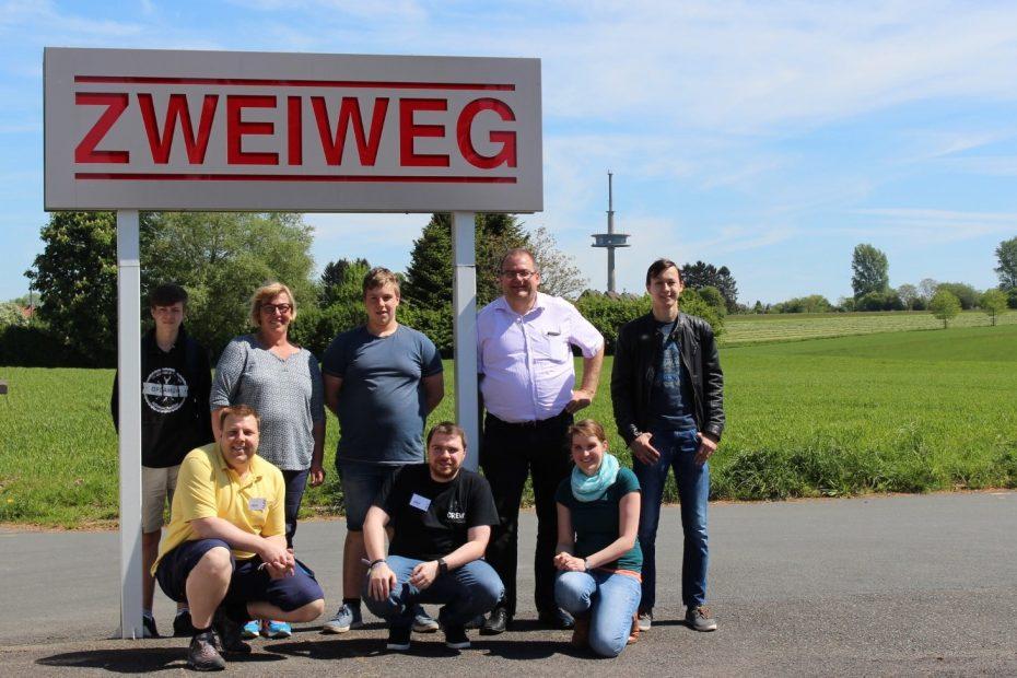 """Eine Gruppe Menschen posiert draußen vor einem Schild mit dem Schriftzug """"Zweiweg"""""""