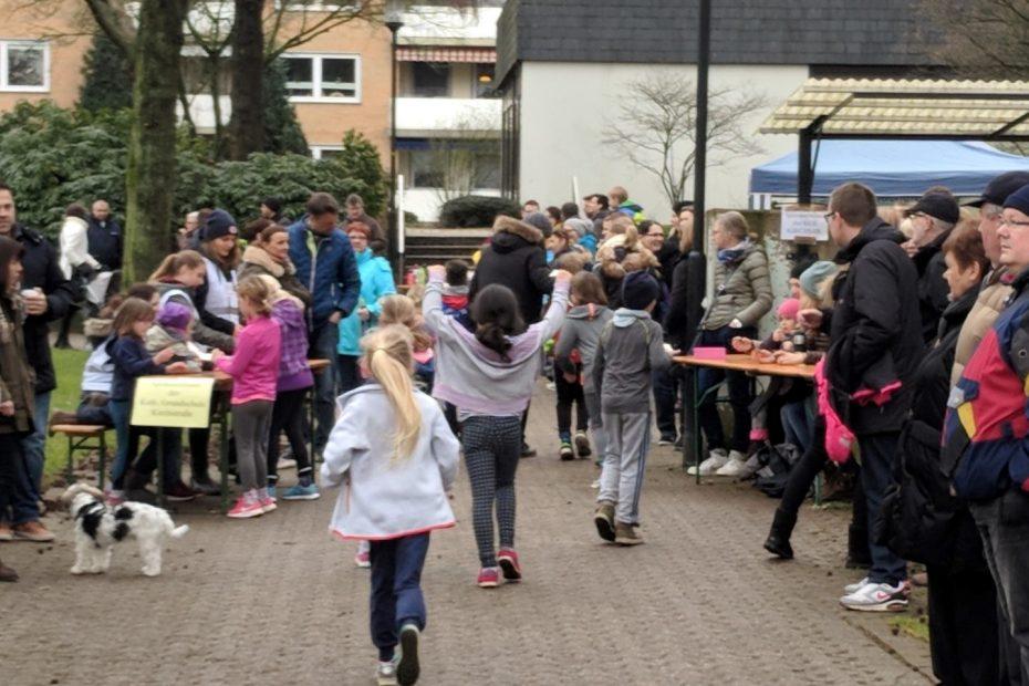 Kinder laufen durch einen Stadtpark. Menschen schauen ihnen zu.