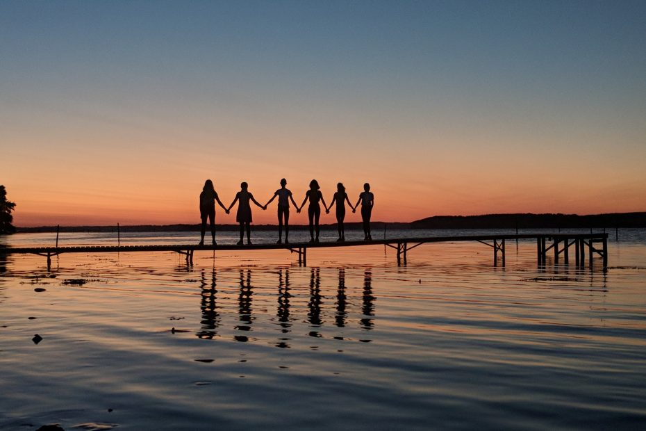 Sechs Jugendliche stehen auf einem Steg auf einem See vor dem Sonnenuntergang und halten sich an den Händen