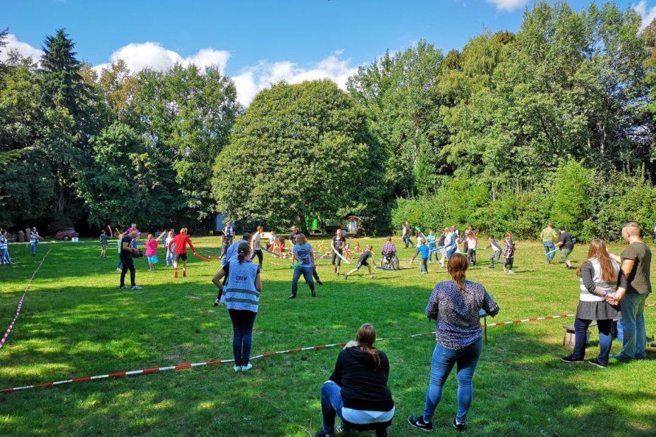 Eine Gruppe Menschen hat Spaß bei einer Poolnudelschlacht in einem mit Flatterband abgesteckten Feld