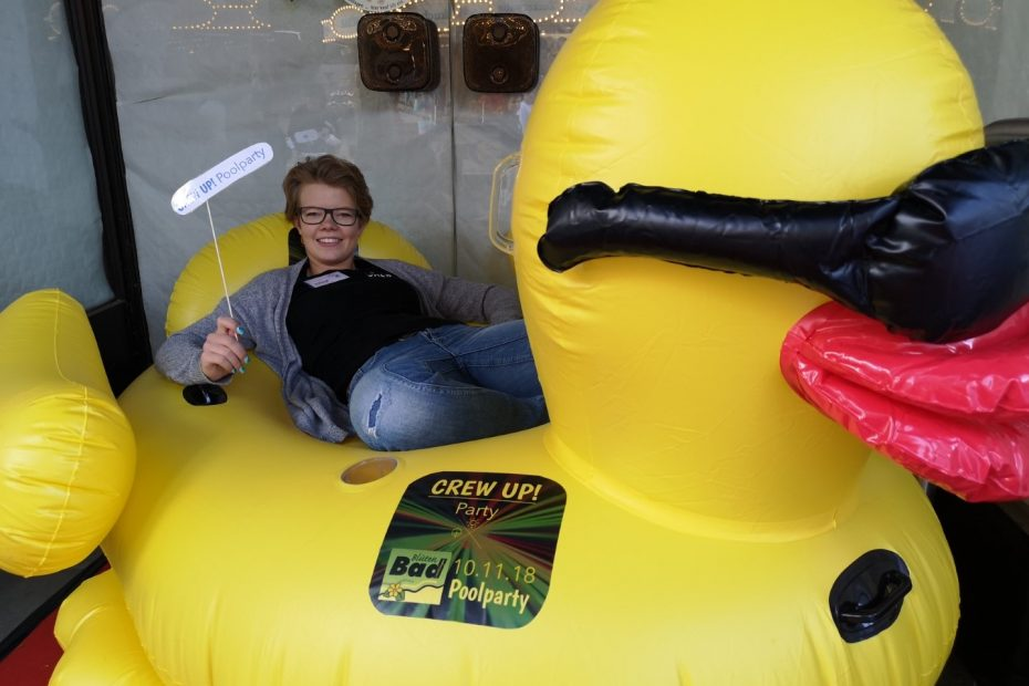 Eine CREW-Ehrenamtlerin liegt auf einer großen, gelben, aufblasbaren Ente
