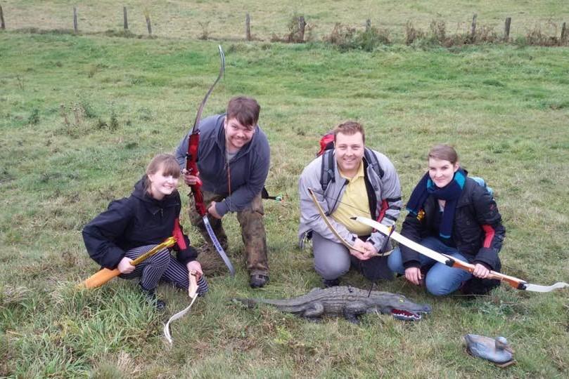 CREW-Ehrenamtler posieren mit Pfeil und Bogen vor einem erlegten Kunst-Krokodil