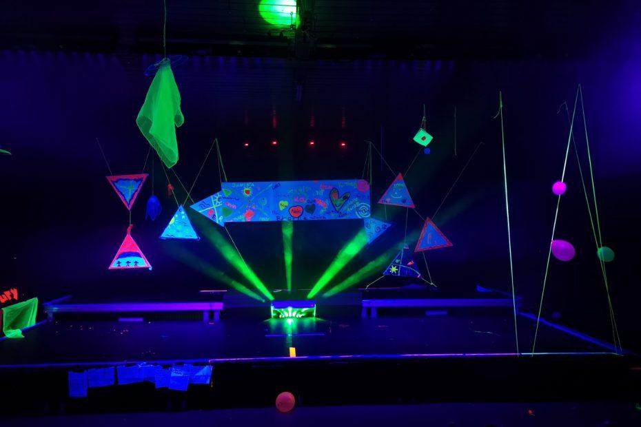 Eine bunt dekorierte Bühne wird von Schwarzlicht angestrahlt