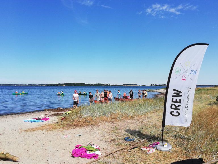Foto von Strandufer mit Kindern und Jugendlichen mit Kanus auf dem Wasser. Eine Beachflag mit CREW-Logo im Vordergrund.