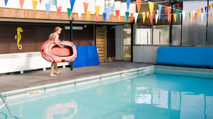 Foto vom Indoor Pool mit Junge mit aufblasbarem Boot am Beckenrand