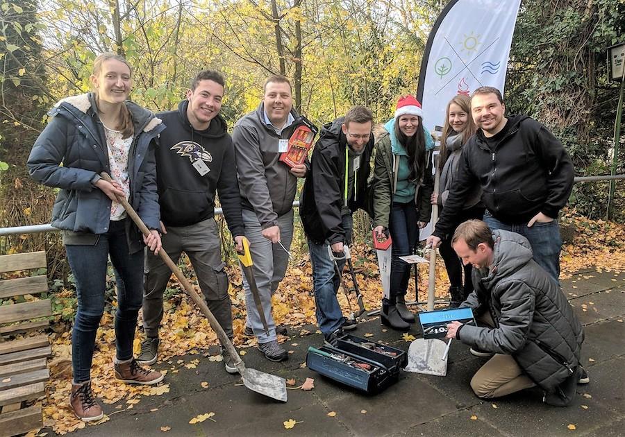 Gruppenfoto von CREW-Mitgliedern im Freien, die eine Werkzeugspende präsentieren
