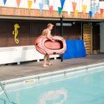 Foto von Indoor Pool mit Junge mit aufblasbarem Boot am Beckenrand