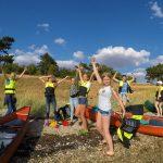 Junge Menschen posieren lachend neben Kanus am Ufer