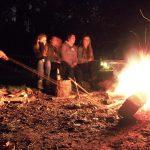 Vier Menschen sitzen an einem Lagerfeuer