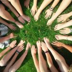 Viele Hände in einem Kreis auf einer Wiese
