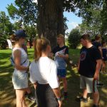 Junge Menschen vor einem Baum auf einer Wiese.
