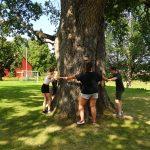 Junge Menschen umarmen einen Baum.