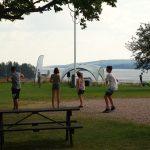 Jugendliche auf einer Wiese vor einem See.
