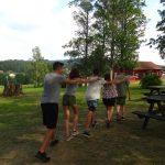 Jugendliche tanzen eine Polonaise um Holztische.