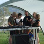 Junge Menschen an einem DJ-Pult.