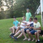 Junge Menschen auf einer Bank auf einer Wiese.