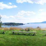 Ausblick über einen See mit Bergen und Wäldern im Hintergrund.