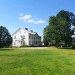 Eine Wiese und ein großes weißes Haus samt Bäumen.