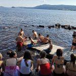 Jugendliche sitzen auf dem Badesteg am See
