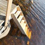 Eine Treppe von einem Steg in einen See.