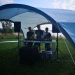 Junge Menschen unter einem Shelter mit DJ-Equipment.