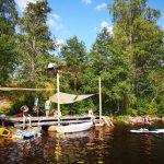 Junge Menschen schwimmen im See und fahren mit Kanus.