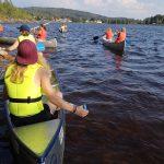 Jugendliche in Kanus auf einem See.