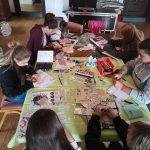 Junge Menschen basteln Reisetagebücher an einem Tisch.