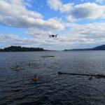 Eine Drohne schwebt über einem See.