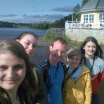 Junge Menschen machen ein Selfie, im Hintergrund ein Haus an einem See.