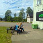 Zwei junge Menschen sitzen auf einer Bank vor einem Geschäft.