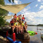 Ein Gruppenfoto von jungen Menschen in Schwimmwesten auf einem Steg.