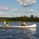 Junge Menschen in einem Kanu auf einem See.