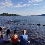 Junge Menschen sitzen am See.