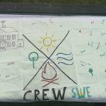 Eine weiße Flagge, mit CREW-Logo bemalt und vielen Unterschriften.