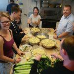 Eine Gruppe junger Menschen schneidet Kartoffeln.
