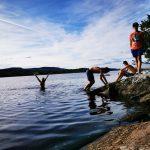 Junge Menschen spielen am Wasser.