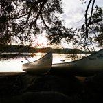 Ein Boot am See vor einem Sonnenuntergang.