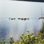 Ein See, ganz klein sind Kanus zu erkennen.