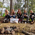 Eine Gruppe junger Frauen sitzt auf einem Baumstamm.