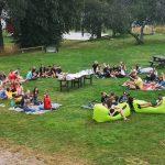Viele junge Menschen picknicken auf einer Wiese.