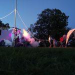 Junge Menschen veranstalten eine Party auf einer Wiese.