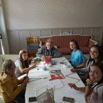Junge Menschen sitzen an einem Tisch und knüpfen Armbänder.