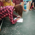 Eine junge Frau zerreist ein Blatt Papier.