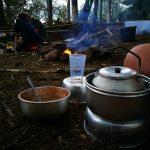 Eine Teekanne, ein Becher und eine Schüssel auf dem Waldboden, im Hintergrund ist ein Lagerfeuer.